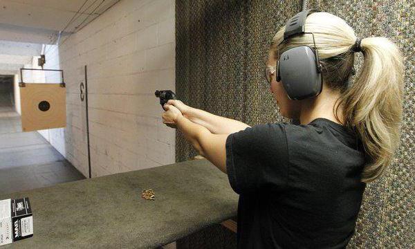 Девушка учится стрелять
